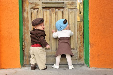 twin boy and girl standing at doorway