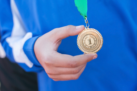 Photo for Hand of the man and medal close up. The winner holds a medal. Victory in competitions. First place. The hand holding a gold medal. - Royalty Free Image