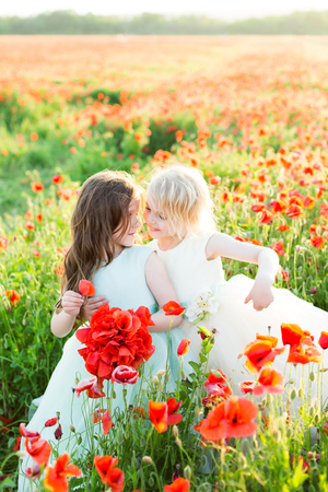 girl model, wedding, poppies, summer fashion concept - two little girls sisters hugged and played with poppies in white and blue wedding dresses, one sister is holding a bouquet of poppies