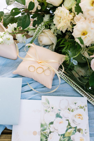 present, surprise, wedding concept. nice top view of little peachy color pillow with thin ribbon, there is three golden rings on it, and nearby few postcards with painting of roses