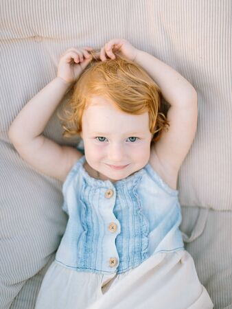 Photo pour portrait of extremely cute little girl with pale skin, curly red hair and charming green eyes, she is dressed in denim sundress - image libre de droit