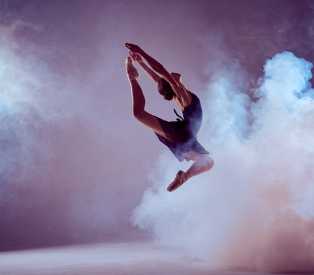 young ballet dancer jumping on a lilac background