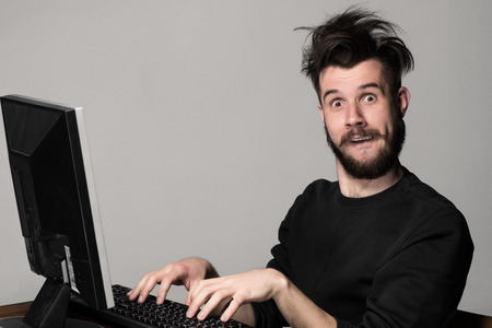 Funny and crazy man using a computer on gray backgroundの写真素材