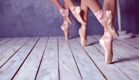 The close-up feet of a three young ballerinas in pointe shoes against the background of the wooden floor