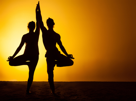 Photo pour The two silhouettes of people practicing yoga in the sunset light - image libre de droit