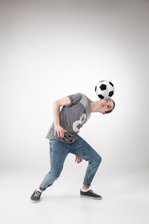 A portrait of a guy with ball on gray background