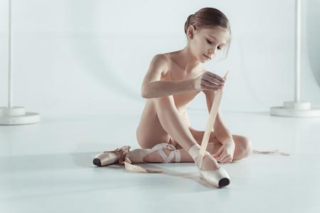 Photo pour Beautiful little ballerina in blue dress for dancing puting on foot pointe shoes - image libre de droit
