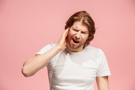 The Ear ache. The sad man with headache or pain on a pink studio background.
