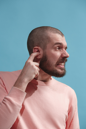 The Ear ache. The sad man with headache or pain on a blue studio background.
