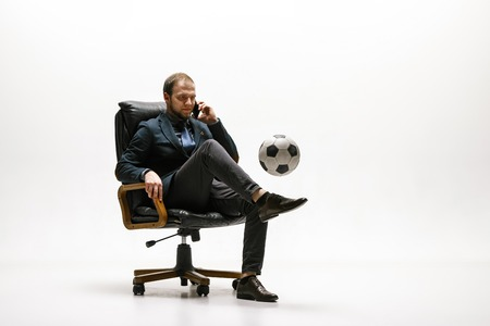 Businessman with football ball in office. Soccer freestyle. Concept of balance and agility in business. Manager perfoming tricks while sitting on chair and speaking on the smartphone isolated on white studio background.