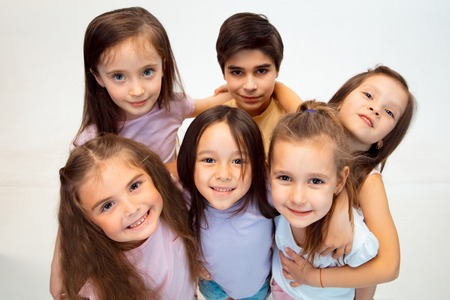 Photo for The portrait of happy cute little kids boy and girls in stylish casual clothes looking at camera against white studio wall. Kids fashion and human emotions concept - Royalty Free Image