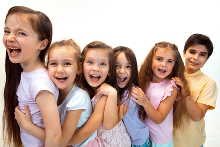 Foto de The portrait of happy cute little kids boy and girls in stylish casual clothes looking at camera against white studio wall. Kids fashion and human emotions concept - Imagen libre de derechos