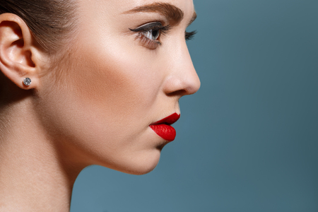 Photo pour Profile highly-detailed beautiful young female face with perfect and clean skin, underlined eyes and red lips against blue studio background. Concept of beauty, care, treatment, health, spa, cosmetics. - image libre de droit