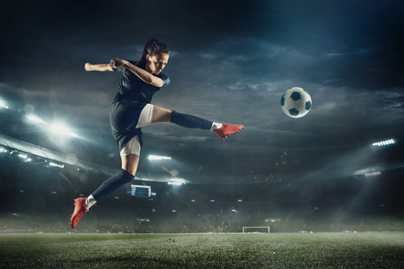 Photo pour Young female soccer or football player with long hair in sportwear and boots kicking ball for the goal in jump at the stadium. Concept of healthy lifestyle, professional sport, hobby, motion, movement. - image libre de droit