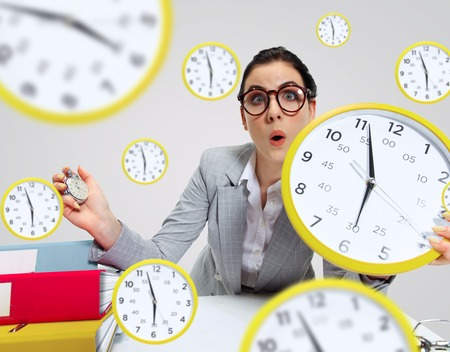 Young woman cant wait to go home from the nasty office. Holding the clock and waiting five minutes before the end. Concept of office workers troubles, business or problems with mental health.