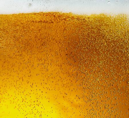 Photo pour Close up view of floating bubbles in light golden colored beer - image libre de droit
