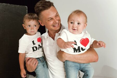 Photo pour Happy father holding adorable little sons and smiling at camera. Young parent with two childs playing and laughting. Family lifestyle. Fathers day, togetherness, parenthood and kids rights concept. - image libre de droit