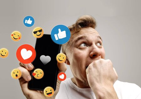 Social media interactions on mobile phone. Internet digital marketing, Chating, commenting, liking. Smiles and icons above smartphone screen, that holding by young man on grey studio background.