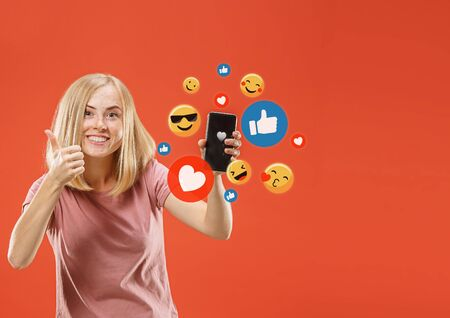 Social media interactions on mobile phone. Internet digital marketing, Chating, commenting, liking. Smiles and icons above smartphone screen, that holding by young woman on red studio background.