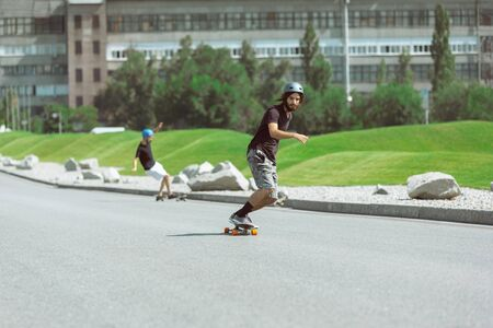 Skateboarders doing a trick at the citys street in sunny day. Young men in equipment riding and longboarding on the asphalt in action. Concept of leisure activity, sport, extreme, hobby and motion.
