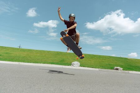 Skateboarder doing a trick at the citys street in sunny day. Young man in equipment riding and longboarding near by meadow in action. Concept of leisure activity, sport, extreme, hobby and motion.