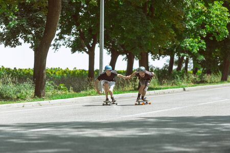 Skateboarders doing a trick at the citys street in sunny day. Young men in equipment riding and longboarding near by meadow in action. Concept of leisure activity, sport, extreme, hobby and motion.