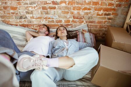 Photo pour Young couple moved to a new house or apartment. Lying together, relaxing after cleaning and unpacking at moved day. Look happy, dreamful and confident. Family, moving, relations, first home concept. - image libre de droit