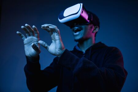 Foto de Young african-american man in VR-glasses in neon light on blue background. Male portrait. Concept of human emotions, facial expression, modern gadgets and technologies. Touching something in gameplay. - Imagen libre de derechos