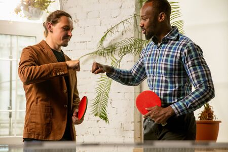 Photo pour Young men playing table tennis in workplace, having fun. Friends in casual clothes play table tennis together at sunny day. Concept of leisure activity, sport, friendship, team-building, teamwork. - image libre de droit