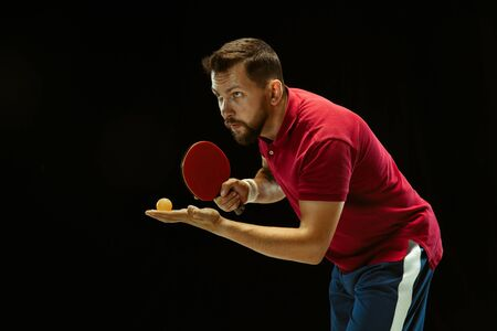 Young man plays table tennis on black studio background. Model in sportwear plays. Concept of leisure activity, sport, human emotions in gameplay, healthy lifestyle, motion, action, movement.