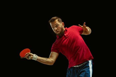 Young man plays table tennis on black studio background. Model in sportwear plays Concept of leisure activity, sport, human emotions in gameplay, healthy lifestyle, motion, action, movement.