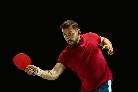 Young man plays table tennis on black studio background. Model in sportwear plays . Concept of leisure activity, sport, human emotions in gameplay, healthy lifestyle, motion, action, movement.
