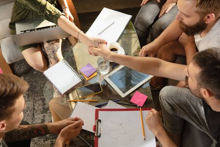 Photo pour Group of young caucasian office workers meeting to discuss new ideas. Creative meeting. Teamwork and brainstorming. Men and women meet in office to plan their future working. Business concept. - image libre de droit