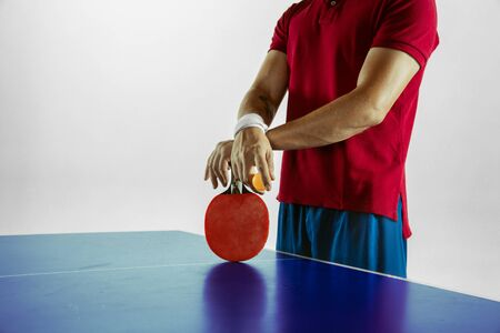 Young man plays table tennis on white studio background. Model in sportwear plays table tennis. Concept of leisure activity, sport, human emotions in gameplay, healthy lifestyle, motion, action, movement.