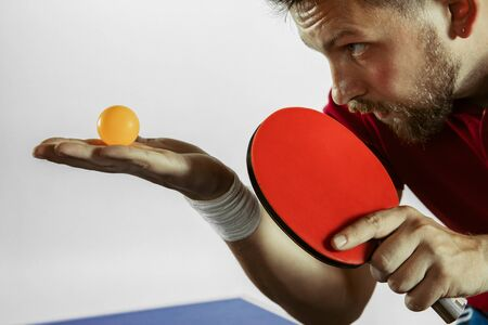 Young man plays table tennis on white studio background. Model in sportwear plays ping pong. Concept of leisure activity, sport, human emotions in gameplay, healthy lifestyle, motion, action, movement.