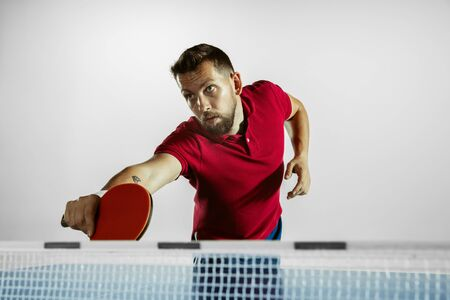Goal. Young man plays table tennis on white studio background. Model plays ping pong. Concept of leisure activity, sport, human emotions in gameplay, healthy lifestyle, motion, action, movement.