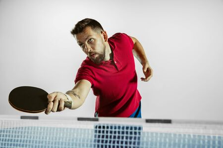 Strong. Young man plays table tennis on white studio background. Model plays ping pong. Concept of leisure activity, sport, human emotions in gameplay, healthy lifestyle, motion, action, movement.