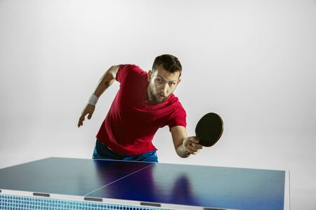 Time. Young man plays table tennis on white studio background. Model plays ping pong. Concept of leisure activity, sport, human emotions in gameplay, healthy lifestyle, motion, action, movement.