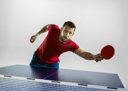 Traffic. Young man plays table tennis on white studio background. Model plays ping pong. Concept of leisure activity, sport, human emotions in gameplay, healthy lifestyle, motion, action, movement.