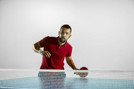 Rush. Young man plays table tennis on white studio background. Model plays ping pong. Concept of leisure activity, sport, human emotions in gameplay, healthy lifestyle, motion, action, movement.