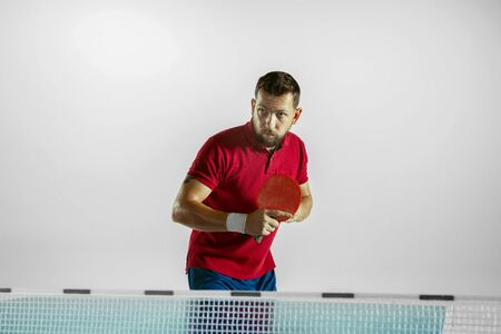 Experiences. Young man plays table tennis on white studio background. Model plays ping pong. Concept of leisure activity, sport, human emotions in gameplay, healthy lifestyle, motion, action, movement.