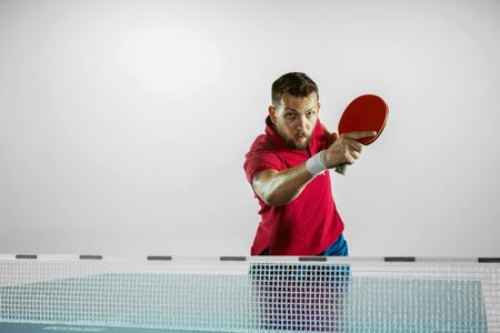 Moment. Young man plays table tennis on white studio background. Model plays ping pong. Concept of leisure activity, sport, human emotions in gameplay, healthy lifestyle, motion, action, movement.