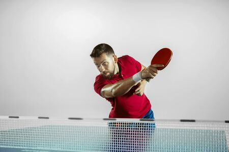Possibility. Young man plays table tennis on white studio background. Model plays ping pong. Concept of leisure activity, sport, human emotions in gameplay, healthy lifestyle, motion, action, movement.