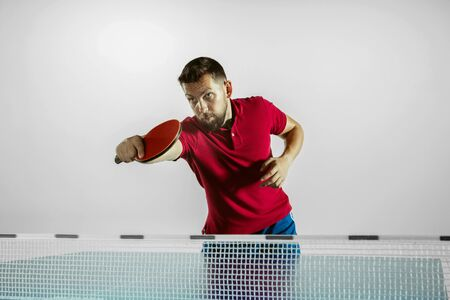 Run. Young man plays table tennis on white studio background. Model plays ping pong. Concept of leisure activity, sport, human emotions in gameplay, healthy lifestyle, motion, action, movement.