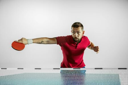 Start. Young man plays table tennis on white studio background. Model plays ping pong. Concept of leisure activity, sport, human emotions in gameplay, healthy lifestyle, motion, action, movement.