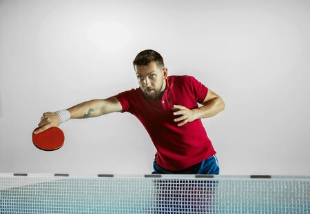 Going up. Young man plays table tennis on white studio background. Model plays ping pong. Concept of leisure activity, sport, human emotions in gameplay, healthy lifestyle, motion, action, movement.