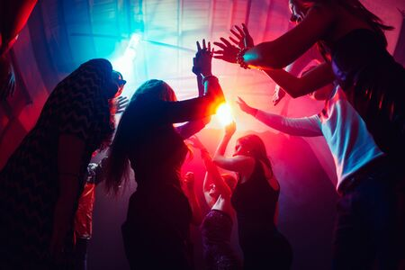 Photo pour Until sunrise. A crowd of people in silhouette raises their hands on dancefloor on neon light background. Night life, club, music, dance, motion, youth. Purple-pink colors and moving girls and boys. - image libre de droit