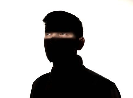 Photo for Dramatic portrait of caucasian young man in the dark isolated on white studio background. Sunlight line on the dark face. Human nature, hidden things, psycology concept. Art elegant creative photo. - Royalty Free Image