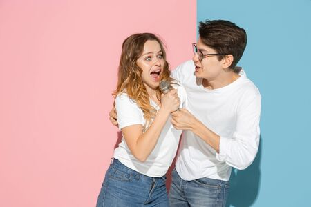 Photo pour Singing song together. Young and happy man and woman in casual clothes on pink, blue bicolored background. Concept of human emotions, facial expession, relations, ad. Beautiful caucasian couple. - image libre de droit