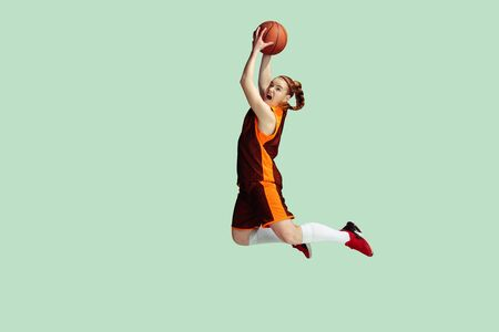 Photo for Young caucasian female basketball player in action, motion in high jump isolated on mint colored background. Concept of sport, movement, energy and dynamic, healthy lifestyle. Training, practicing. - Royalty Free Image